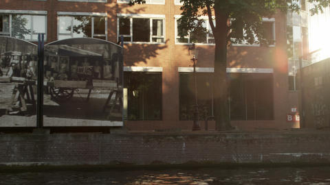 Tracking shot of buildings and stalls along the Amsterdam Canal with lens flare  Footage