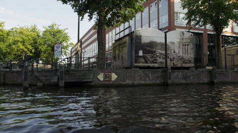 Tracking shot of downtown Amsterdam along the canal in Netherlands with lens fla Footage