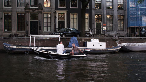 AMSTERDAM, NETHERLANDS - CIRCA 2013: Tracking shot of two men riding a boat on 2 Footage