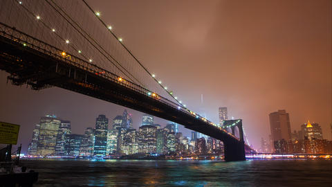 Time lapse of the Brooklyn Bridge overlooking the East River to Manhattan at nig Footage
