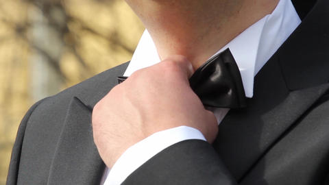 Bridegroom who arranges bow tie at the neck before going to church Live Action