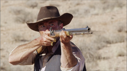 Slow motion of cowboy lifting his rifle to shoulder and aiming gun Footage