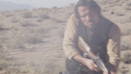 Cowboy turning and lifting rifle to shoot Footage