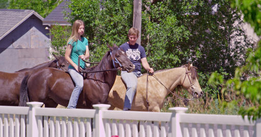 2 women riding horses as viewed from yard Footage