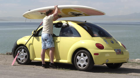 View of man shutting door to yellow car and grabbing surfboard off the top Live Action