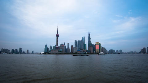 Wide time lapse of boats floating by with towers in the back in Shanghai China,  Footage
