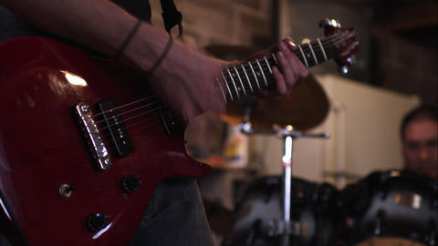 Panning view of man playing electric guitar with drummer in the background Footage