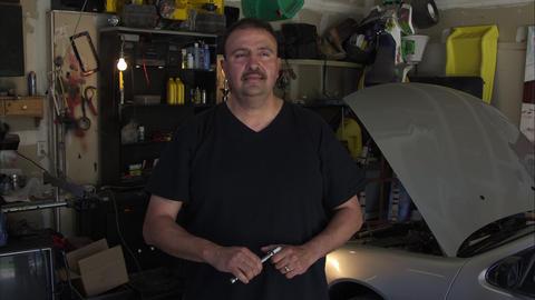 Static shot of a handyman in a dimly lit garage Footage