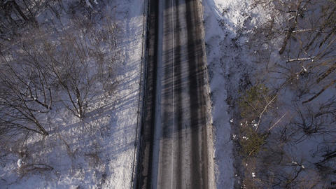 Aerial - Driving cars on a rural road in winter Footage