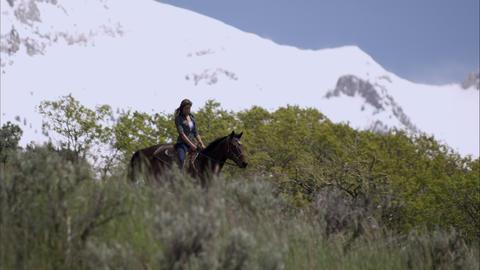 Slow motion shot of a woman on horseback descending a hill Footage