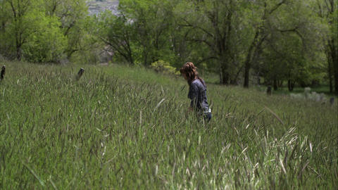 Slow motion shot of a woman walking through tall grass Footage