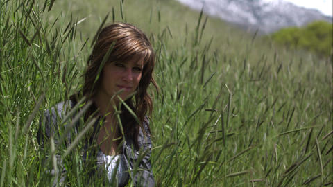 Slow motion shot of a smiling young woman seated in tall grass Footage