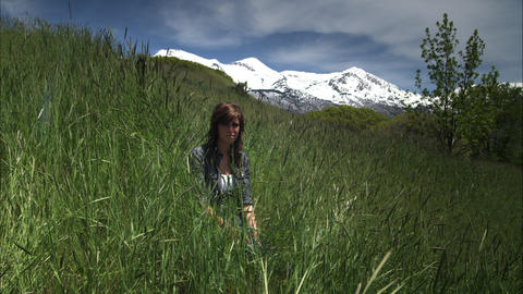 Slow motion shot of a young woman seated in tall grass with mountains behind her Footage
