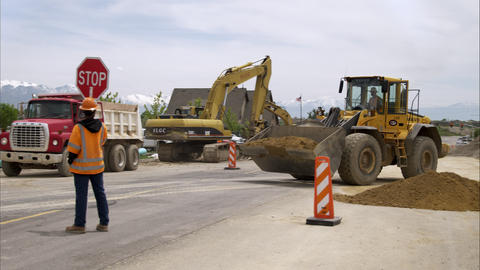 Static shot of a man holding a stop sign and a bulldozer Footage