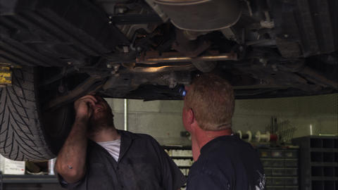 Slow motion shot of two mechanics under a car Footage