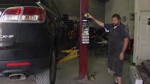 Slow motion of a scruffy mechanic in a garage Footage