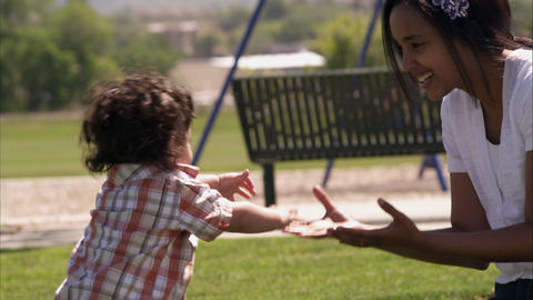 Slow handheld shot of an Indian mother and her son playing at the park Footage