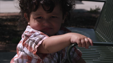 Handheld slow motion shot of a toddler and his mom at a park Live Action