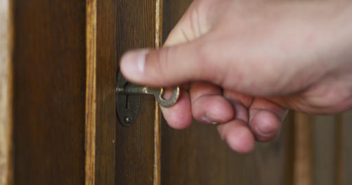 Person by hand turns old key in the keyhole of antique wooden cabinet Live Action