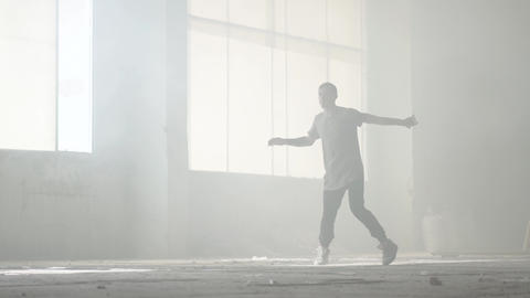 Skillful young great hip-hop dancer performing in the fog. Hip hop culture Live Action