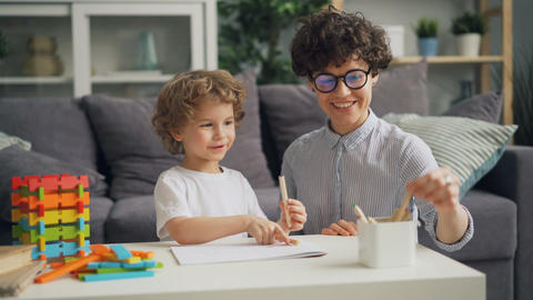Small boy drawing with coloured pencils with caring mother in cozy room at home Footage
