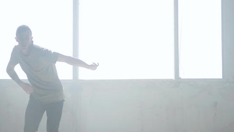 Confident young passionate hip-hop dancer performing in the fog. Hip hop culture Live Action