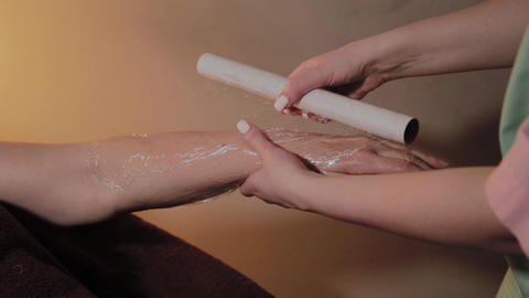 hands wrapped in cellophane by an old woman after hand massage Footage