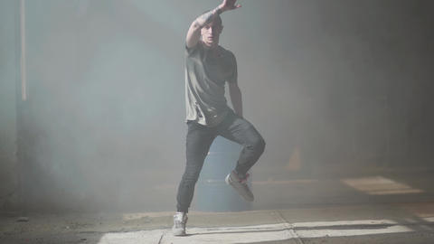 Skillful young passionate hip-hop dancer performing. The man stretches his arms Live Action