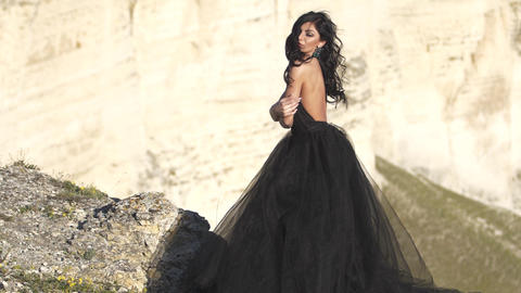 Young woman in black evening dress at backdrop of cliff Wind blow her black hair Live Action