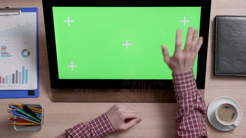 Man's hands touch the top right corner of a green screen on touch monitor Live Action