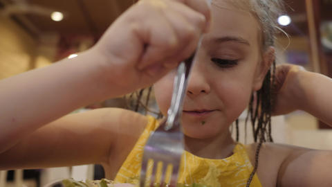 little girl eat green salad with appetite in the restaurant. Good health concept Footage