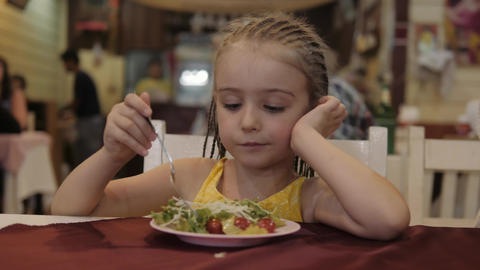little girl eat green salad with appetite in the restaurant. Good health concept Live Action