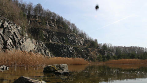 Slow motion splash with stone in swamped quarry, Czech republic Footage