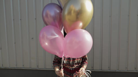 Pretty woman in dress holding balloons with helium outdoors in daylight Footage