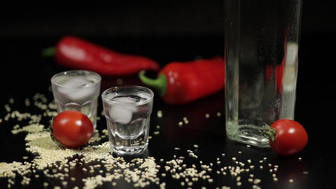 Sparse sesame seeds to two cups of vodka near bottel with vodka Live Action