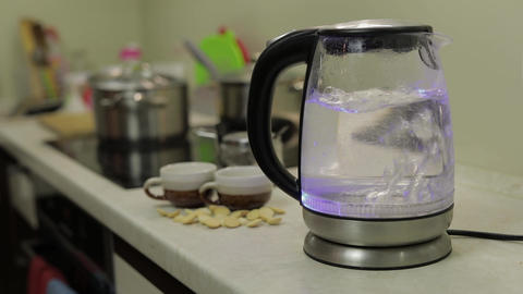 Tea kettle with boiling water. Tea bags and sugar on the background Live Action