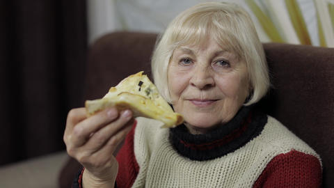 Beautiful elderly woman is sitting on sofa and eats pizza Live Action