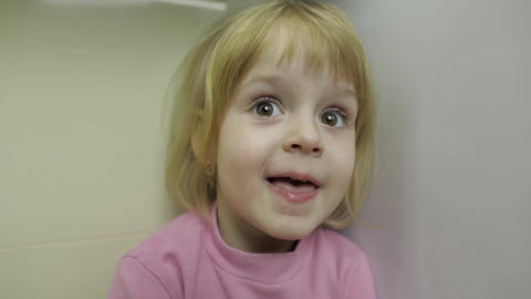 Close up of a little blonde cute girl face. Girl smiling. Inside. Portrait shot Footage