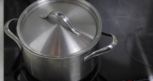 Boiling Water In The Pan that is covered with a lid in the kitchen Live Action