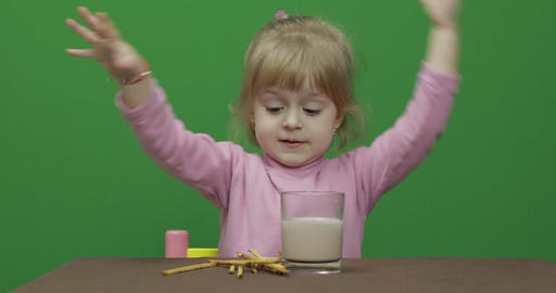 The child eats cookies. A little girl is eating cookies sitting on the table Footage