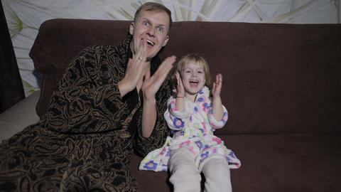 Small daughter with her father watching interesting film with great emotions Footage