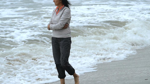 Attractive woman walking the beach Footage