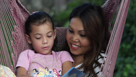 Handheld panning shot of an Asian mother and daughter reading a book on a hammoc Footage