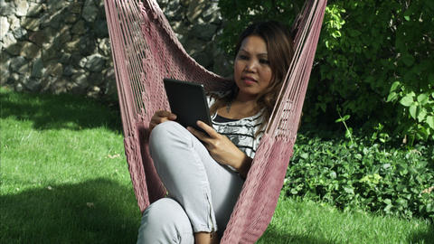 Handheld shot of an Asian woman using a tablet while sitting on a hammock Footage