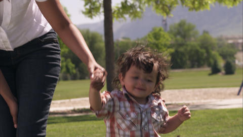 Slow handheld shot of an Indian mother and her son walking in the park Footage