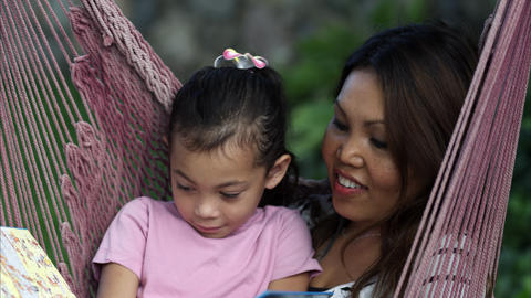 Handheld shot of an Asian mother and daughter reading a book on a hammock Live Action