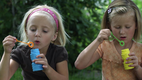 Handheld shot of two little girls blowing bubbles Footage