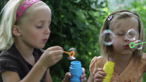 Slow handheld shot of two little girls blowing bubbles Footage