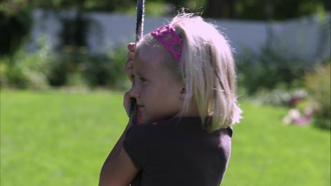Slow motion tilt shot of a little girl sitting on a tree swing Footage
