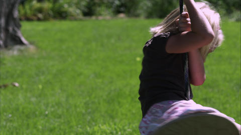 Tilt shot of a little girl playing on a tree swing in slow motion Live Action